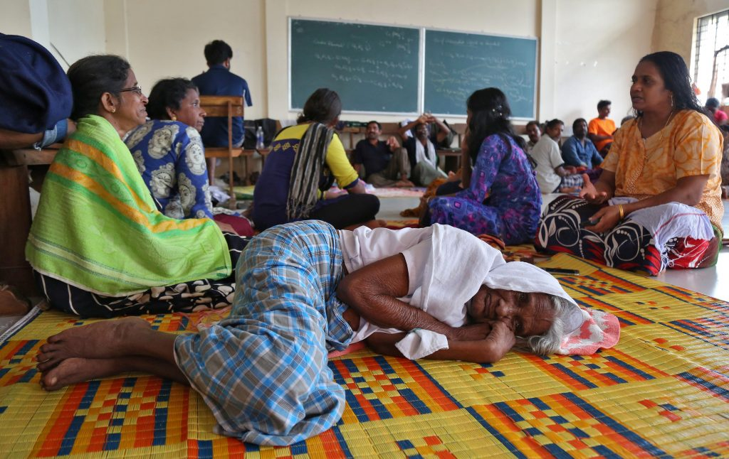 Flood victims rest inside a university classroom, which is converted into a temporary relief camp in Kochi